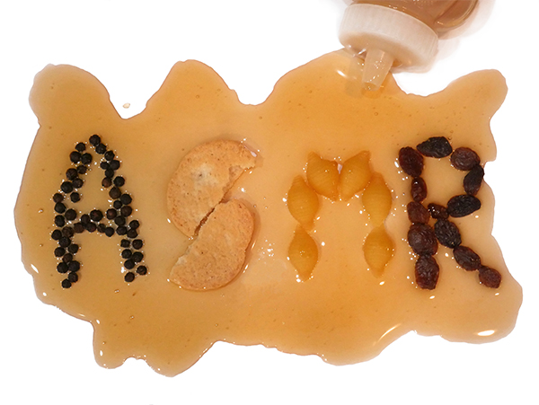 """An opaque blob of honey on a white table; """"ASMR"""" is spelled out in pantry staples like pepper seeds, uncooked pasta, raisins and a cookie."""