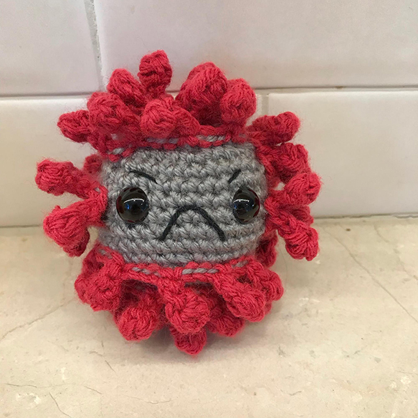A photograph of a small grey crocheted virus with red spiked protruding from it, and it has a black frowny face.