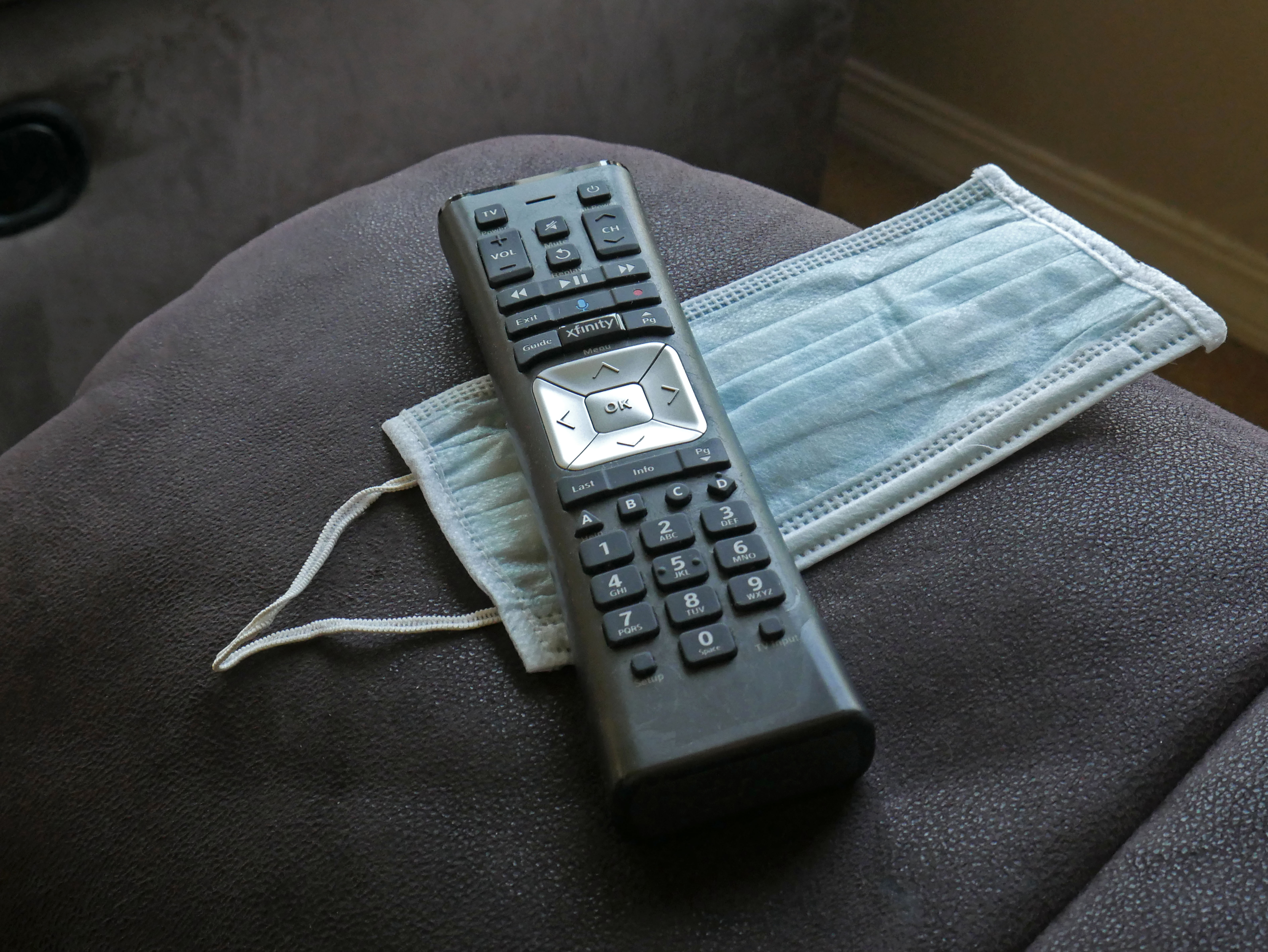 A photograph of a TV remote resting on top of a surgical mask.