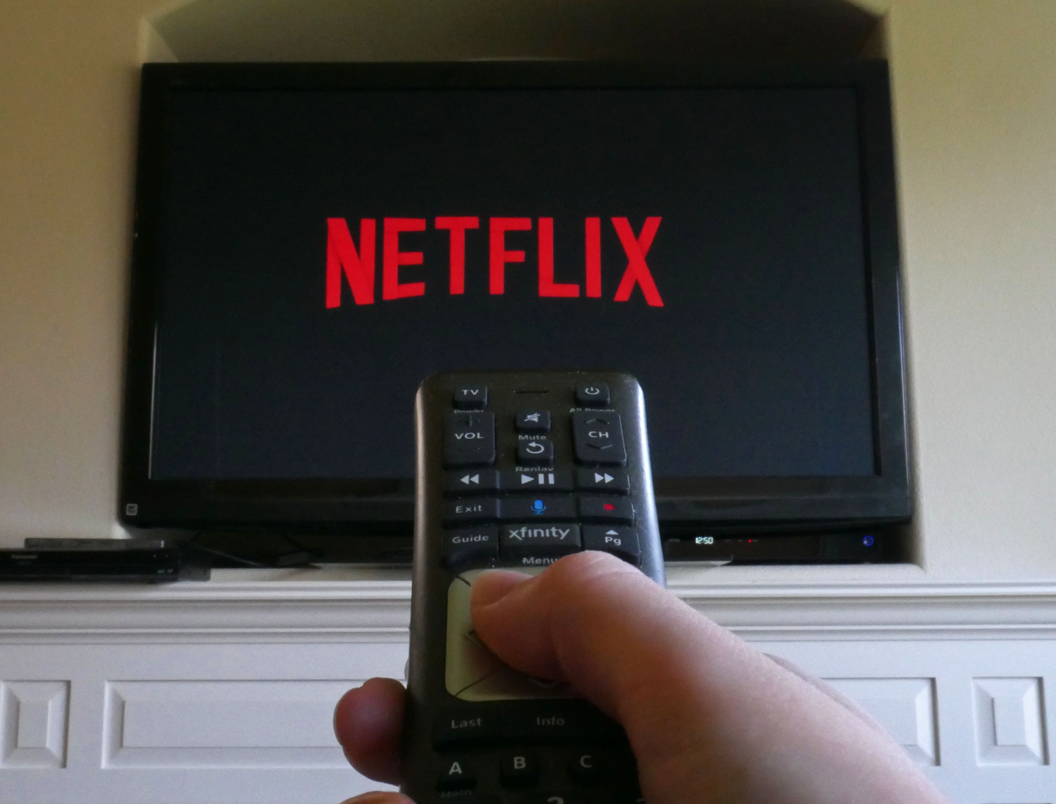 A photograph of a human hand pointing a TV remote control at a flat screen that says 'Netflix' in its signature red hue.