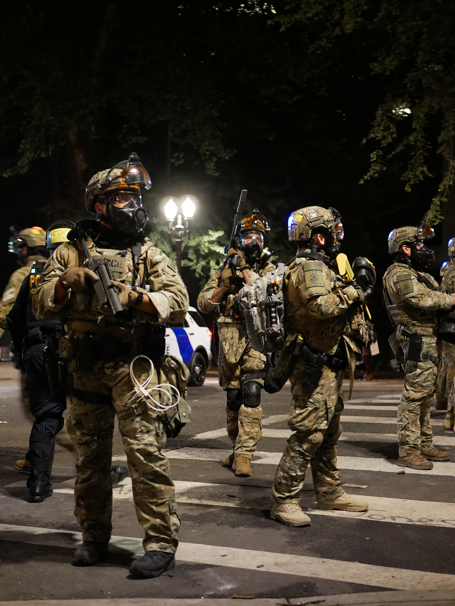 Photograph of police officers dressed in full camouflage protective gear on the streets of downtown PDX.